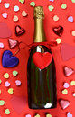 Valentines day candy and champagne a bottle of surrounded by hearts assorted Royalty Free Stock Photography