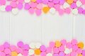 Valentines day candy hearts double border over white wood sugar forming a a background Stock Photos
