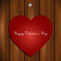 Valentines day card red heart hanging on wooden background for Stock Photography