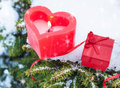 Valentines day or christmas winter still life with gift and candle outdoor heart shaped red on snowy pine branch Stock Photos