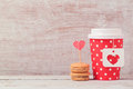 Valentines day concept with paper coffee cup and macarons. Romantic coffee shop