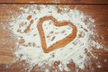 Valentines day heart in flour on wooden table Stock Photos