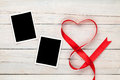 Valentines day heart shaped red ribbon and blank photo frames over wooden table background Royalty Free Stock Photography