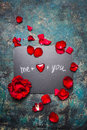 Valentines day lettering background on chalkboard with red hearts and rose petals, top view
