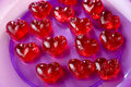 Valentines day red sweet candies in heart shape into a purple plate Royalty Free Stock Photography
