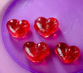 Valentines day red sweet candies in heart shape into a purple plate Stock Image