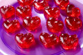 Valentines day red sweet candies in heart shape into a purple plate Royalty Free Stock Photos