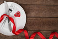 Valentines day table setting with plate, fork, knife, red heart, ring and ribbon.   background Royalty Free Stock Photo