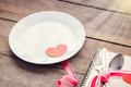 Valentines day table setting with plate, knife, fork, red ribbon Royalty Free Stock Photo
