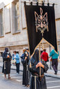 Valladolid good thursday spain – april black nazarenos with a flag in the religious processions with a musical band behind Royalty Free Stock Image