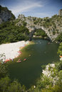 Vallon pont d arc a natural bridge in the ardeche france stone arch over river with lots of kayaks Stock Photos