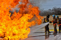 Valve on fire with high flames gas burning firemen fighting Royalty Free Stock Images