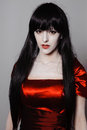 Vamp woman young mysterious fashion witch vampire with black hairs against the dark background Royalty Free Stock Image