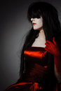 Vamp woman young mysterious fashion witch vampire with black hairs against the dark background Stock Photo