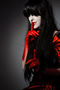 Vamp woman young mysterious fashion witch vampire with finger on the lips against the dark background Royalty Free Stock Photos