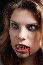 Vampire with the bloody teeth girl intense look and bleeding mouth Royalty Free Stock Photos