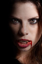 Vampire with the bloody teeth girl intense look that comes from darkness Stock Photo