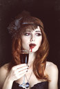 Vampire woman redhead with glass of blood photo in vintage style Stock Image