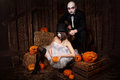 Vampires with halloween pumpkin portrait of a men and sexy women against wooden background shot in a studio Royalty Free Stock Images