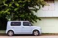 Van cars rectangular light blue four door parked next to the house Stock Images
