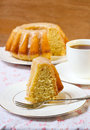 Vanilla and cinnamon bundt cake with icing cup of tea Stock Image