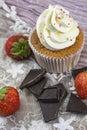Vanilla cupcake with white cream, dark chocolate and strawberries Royalty Free Stock Photo