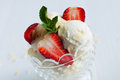 Vanilla ice cream with almonds and strawberries creamy fresh mint leaves in a crystal bowl on a white wooden board sweet summer Royalty Free Stock Images