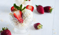 Vanilla ice cream with almonds and strawberries creamy fresh mint leaves in a crystal bowl on a white wooden board sweet summer Stock Photography