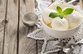 Vanilla ice cream with mint leaves in white bowl on rustic wooden background Royalty Free Stock Photo