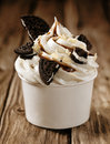 Vanilla ice cream with oreos and chocolate sauce takeaway tub filled a swirl of pieces of oreo biscuits close up view on old Stock Image