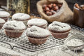 Vanilla muffins decorated with icing sugar on old wooden table Stock Photos