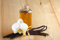 Vanilla pods flower and bottle on a wooden background Royalty Free Stock Images