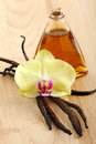 Vanilla pods flower and bottle on a wooden background Stock Photography