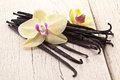 Vanilla sticks with a flower on white wooden table Stock Photo