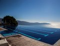 Vanishing edge on top of the world a pool seems to fall into lake garda far below a crystal clear day Royalty Free Stock Photos