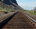 Vanishing point train tracks leading to mountains Stock Images