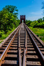 Vanishing point view of an old iron railroad trestle with iconic truss bridge over the brazos river texas Royalty Free Stock Photo