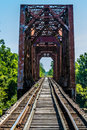 Vanishing point view of an old railroad trestle with an old iron truss bridge over the brazos river iconic texas Stock Image