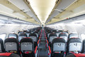 Vanishing row of black and red seats in airplane modern interior aircraft inside symmetric inside air transport economy Stock Image