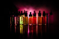Vape concept. Smoke clouds and vape liquid bottles on dark background. Light effects. Useful as background or vape advertisement o