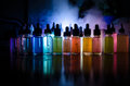 Vape concept. Smoke clouds and vape liquid bottles on dark background. Light effects. Useful as background or vape advertisement o Royalty Free Stock Photo
