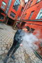 Vape man. A handsome young white guy in glasses blows steam from an electronic cigarette in a vintage old red yard.