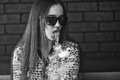 Vape. Young handsome white girl in sunglasses is admiting puffs of steam from the electronic cigarette. Teenager. Black and white. Royalty Free Stock Photo