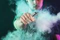 Vaping man holding a mod. A cloud of vapor. Royalty Free Stock Photo