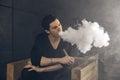Vaping man holding a mod. A cloud of vapor. Black background. Royalty Free Stock Photo