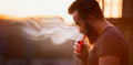 Vaping, young man with a beard, produces vapor sunset sky background, place for text