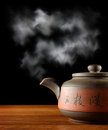 Vapor of hot teapot standing on wooden table black background Royalty Free Stock Photos