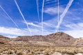 Vapor trails over desert mountains in death valley Royalty Free Stock Image