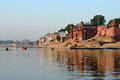 Varanasi ghats temples towering over the lining the ganges river at Stock Photo