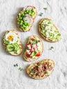 Variation avocado sandwich - with crispy bacon, quail egg, tomatoes, goat cheese, green peas, radish, cucumber. Healthy snack. On
